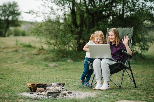 Kommunikation mit familie online auf laptop in der nähe von feuer in der natur