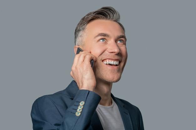 Kommunikation, smartphone. glücklicher jubelnder mann in grauer businessjacke mit einem zahnigen lächeln, das per smartphone nach oben kommuniziert