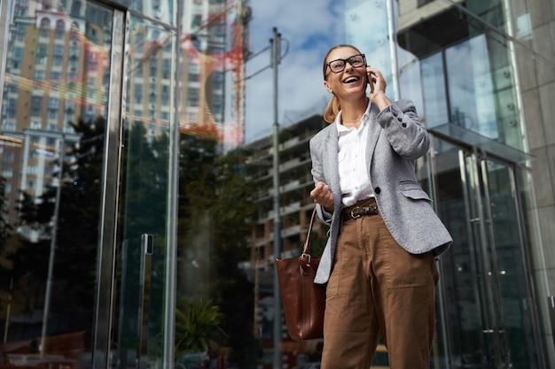 Kommunikationsporträt einer glücklichen, modischen geschäftsfrau mit brille und klassischer kleidung