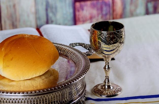 Kommunion nehmen schale glas mit rotwein, brot und heiliger bibel auf holztisch