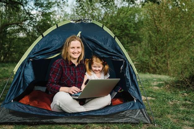 Kommunizieren sie mit verwandten, familie online auf laptop im zelt in der natur