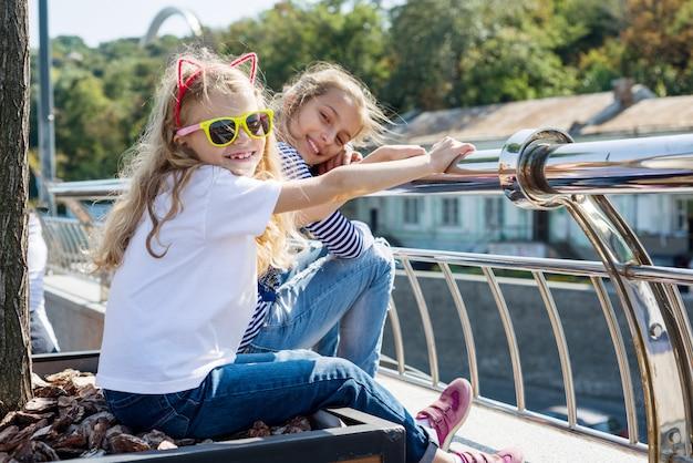 Kommunizieren und entspannen sie die kinder von zwei mädchen. städtischer hintergrund