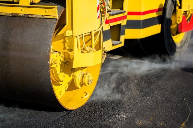 Kompakte dampfwalze glättet den asphalt