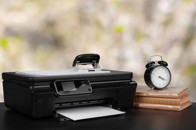 Kompakter heimdrucker auf dem schreibtisch mit büchern vor unscharfem hintergrund, nahaufnahme