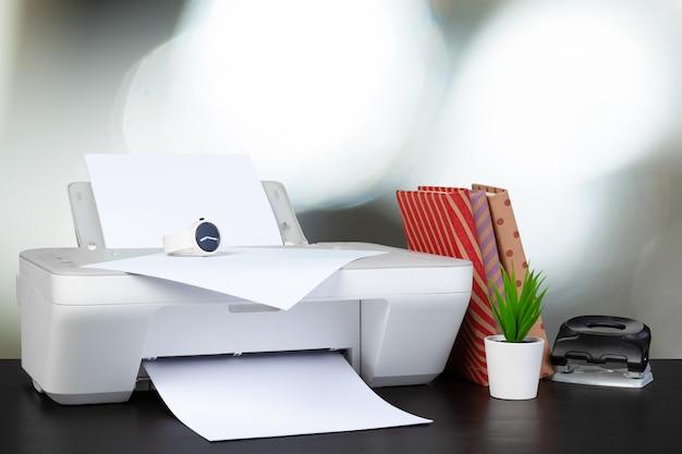 Kompakter heimdrucker auf dem schreibtisch mit büchern vor unscharfem hintergrund