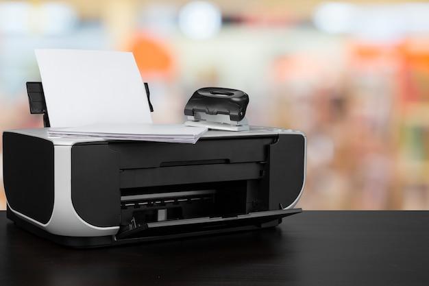Kompakter laserdrucker auf schwarzem schreibtisch vor verschwommenem hintergrund