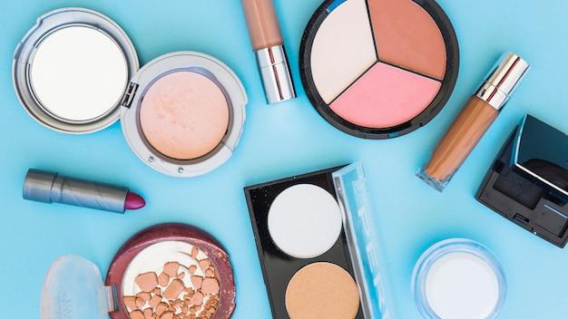 Kompaktes pulver; lippenstift; stiftung auf blauem hintergrund