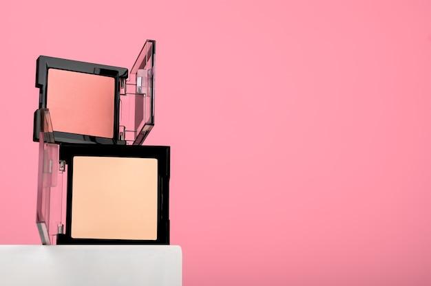 Kompaktes rouge und puder auf einem weißen ständer, ein schaufenster für kosmetische schönheitsprodukte. professionelles mineralisches nude-puder für damen-make-up. rosa rouge weibliches accessoire. platz kopieren.