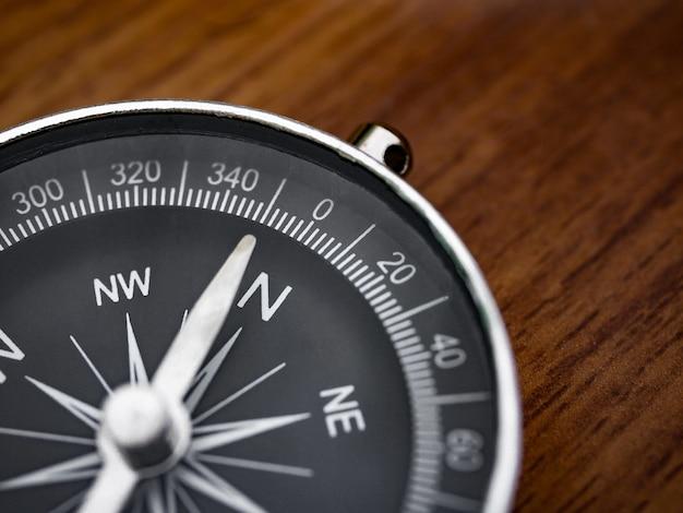 Kompass auf dem braunen holztischhintergrund