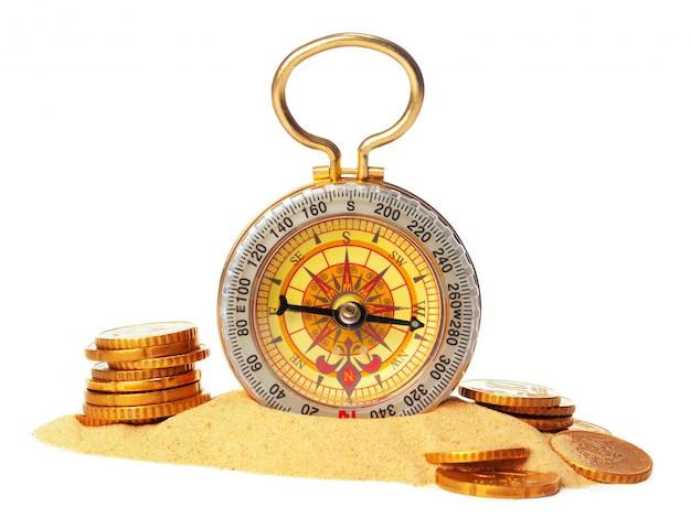 Kompass auf dem meersand und münzen Premium Fotos