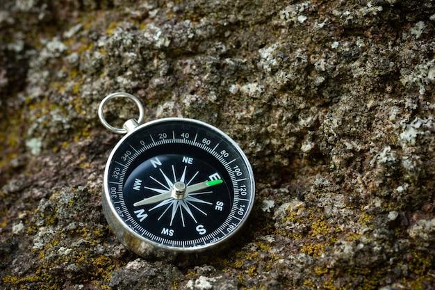 Kompass auf den felsen im wald gelegt. nahaufnahme und kopierraum. konzept der dschungel-abenteuerreise.