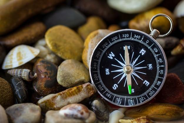 Kompass auf den kieseln und muscheln am flussufer.