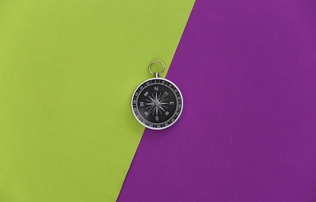 Kompass auf lila grünem hintergrund. ansicht von oben. minimalismus-reisekonzept. flach legen