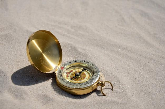 Kompass auf sandhintergrundnahaufnahme