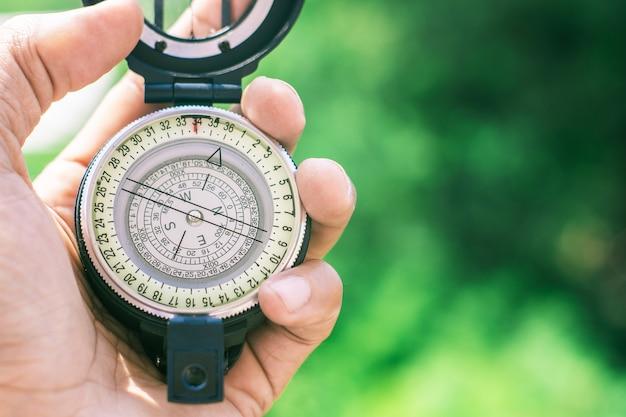 Kompass auf unscharfem hintergrund halten.