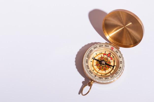 Kompass auf weißer hintergrundnahaufnahme mit harten schatten mit kopienraum.
