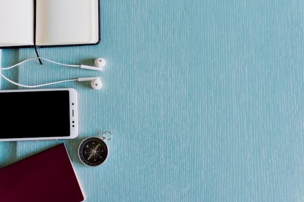 Kompass, handy, stift und notizbuch auf blauem hintergrund copyspace