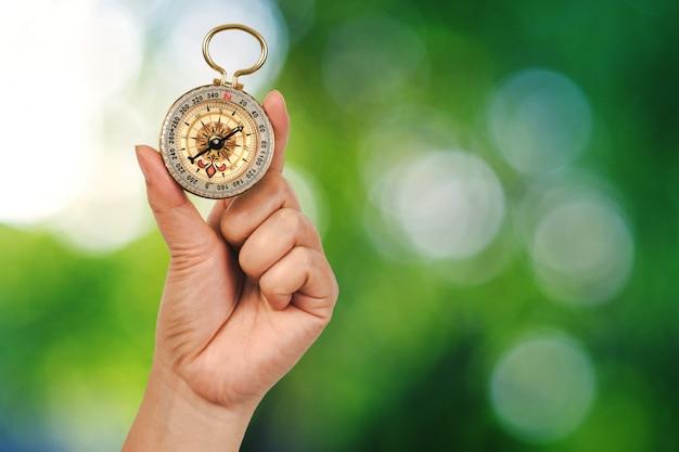 Kompass in der hand mit naturhintergrund