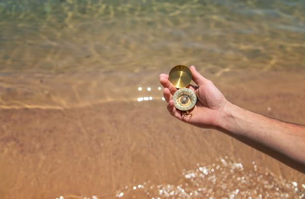Kompass in der hand vor dem hintergrund des meeres. selektiver fokus. natur.