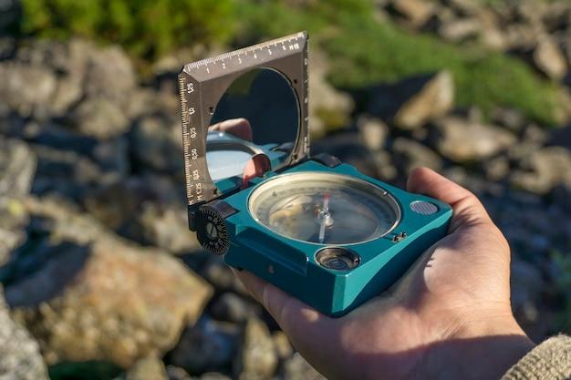Kompass in der hand vor dem hintergrund einer verschwommenen bergwaldlandschaft