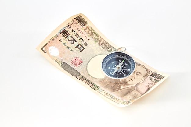 Kompass mit banknoten der japanischen yen und japanische yen prägen auf weißem hintergrund
