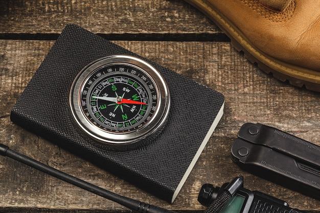Kompass umgeben von bergwerkzeugen auf holztisch