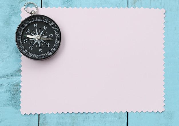 Kompass und briefpapier auf dem blauen bretterboden.