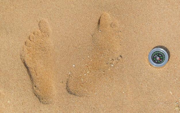 Kompass und fußspuren im sand
