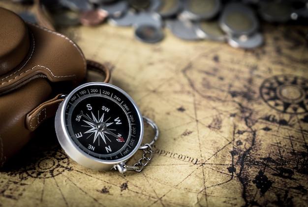 Kompass und kamera auf weinlesekarten-kopienraum