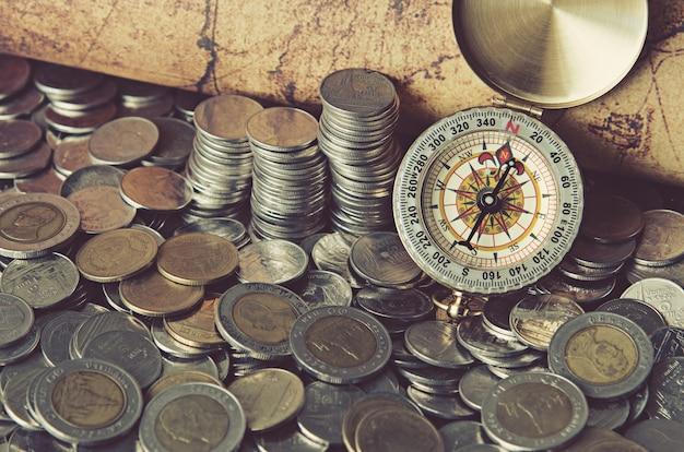 Kompass und münzen auf alte karte