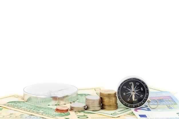 Kompass und münzen auf geld banknoten euro und dollar