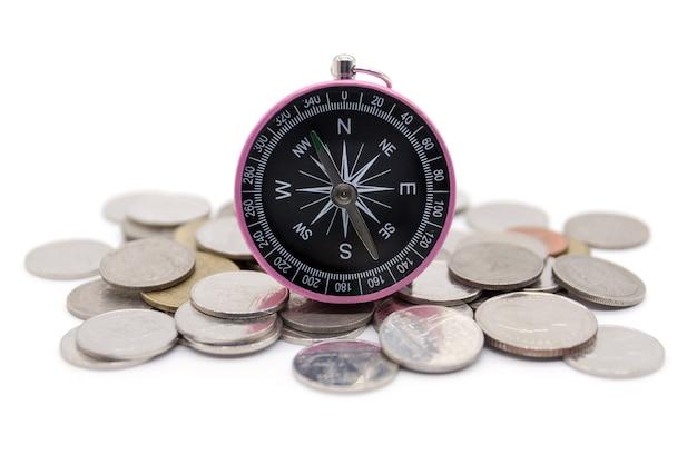 Kompass und münzen auf weißem hintergrund