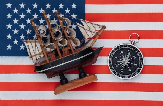 Kompass und schiff auf usa-flagge hautnah. ansicht von oben