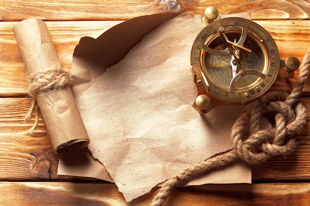 Kompass und seil auf alten holzbrettern