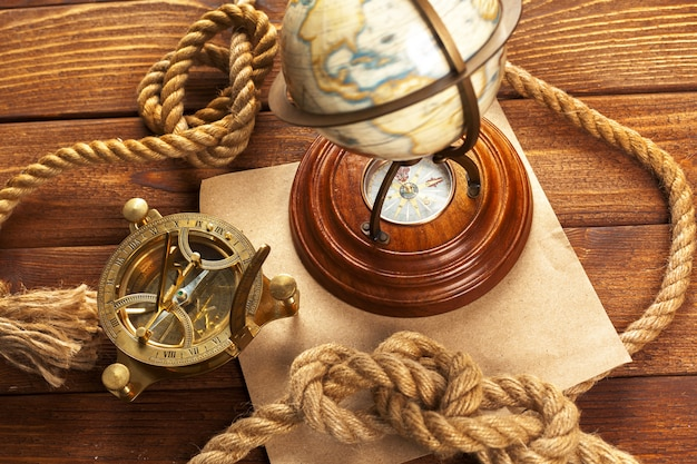Kompass und seil auf holztisch. nahansicht Premium Fotos