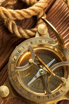 Kompass und seil auf holztisch.