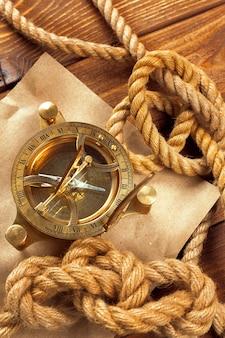 Kompass und seil auf holztisch