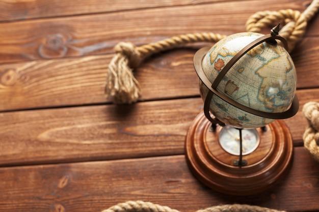 Kompass und seil auf holztischhintergrund