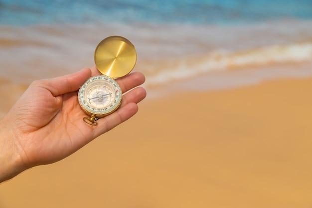 Kompass zur hand im meer und am strand.