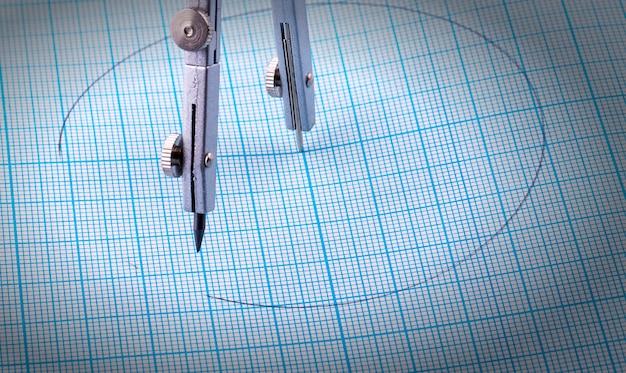 Kompasskompasse und ein kreis gemalt auf blauem millimeterpapier