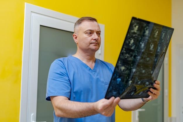 Kompetenter arzt, der röntgenbilder auf dem magnetresonanztomographen liest.