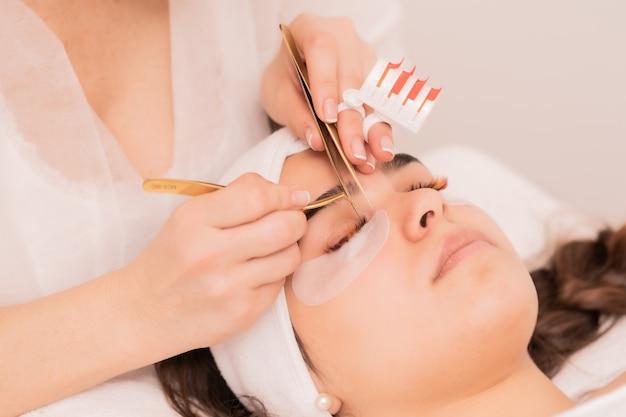 Kompetenter kosmetiker, der das verfahren zur wimpernverlängerung durchführt
