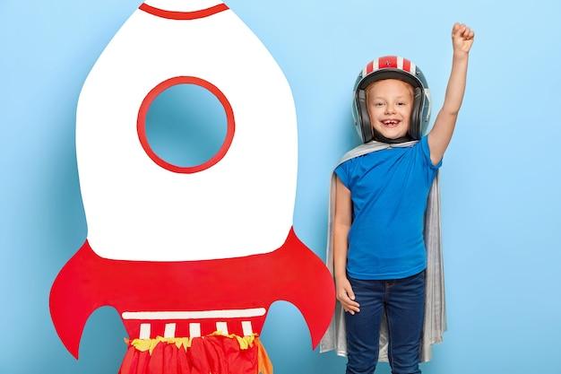 Komplett flugbereit! das lächelnde kleine kind spielt mit dem papierspielzeugflugzeug, hält die arme hoch und spielt ein interessantes spiel