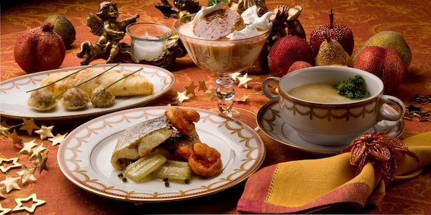 Komplettes menü, tischservice mit orangefarbenem hintergrund und barocker dekoration von kerzen und früchten