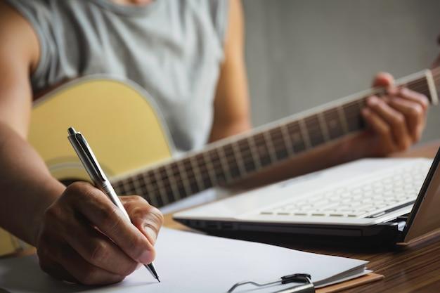 Komponist hält bleistift und schreibt texte in papier. musiker spielt akustische gitarre.