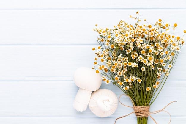 Komposition aromatherapie mit naturkosmetik und kamillenblüten auf hellem hintergrund.