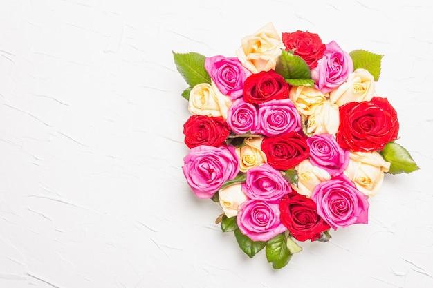 Komposition aus frischen bunten rosen auf keramikständer. das festliche konzept für hochzeiten, geburtstage, 8. märz, mutter- oder valentinstag. grußkarte, flach, weißer kitthintergrund