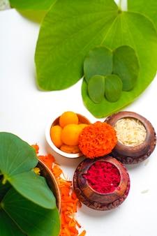 Komposition aus grünen blättern, reis und süßigkeiten für das indische festival dussehrae
