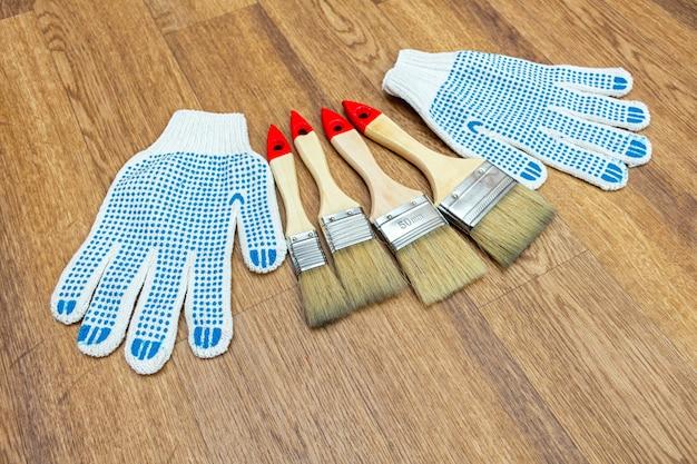 Komposition aus malwerkzeugen mit pinseln, handschuhen und farbroller auf dem holz