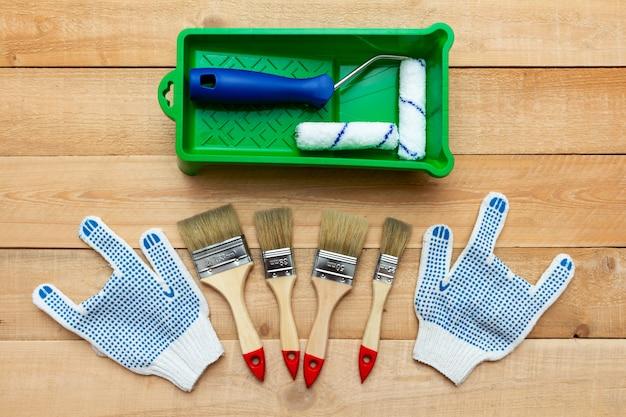 Komposition aus malwerkzeugen mit pinseln, handschuhen und farbroller auf dem holztisch